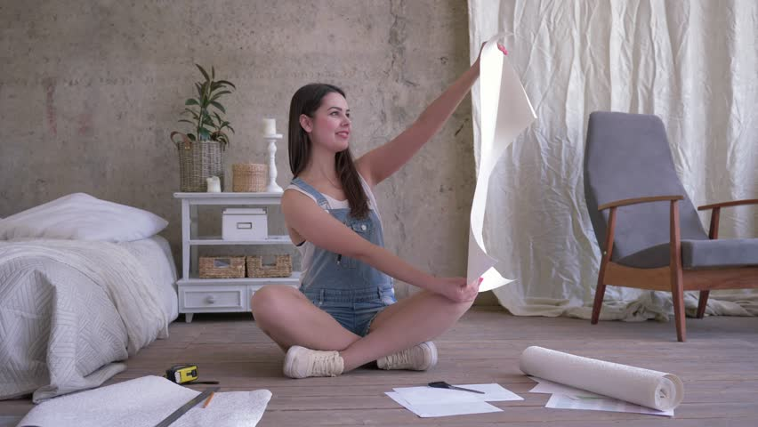 Repair in a new apartment, beautiful happy young woman looks on a cut piece of wallpaper sitting on floor on background of unpainted wall | Shutterstock HD Video #1027362302