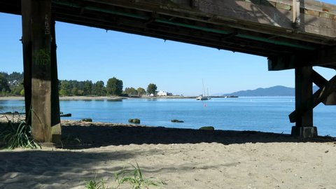 4K: Shot of container ships and sailboats on Burrard Inlet with walking bridge in foreground.