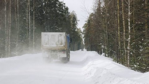 A truck carrying ore rides along a narrow winter forest road. Slow motion.