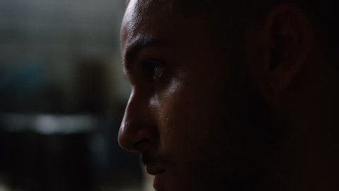 Profile of criminal being surrounded by special ops military SWAT team members crouched down in warehouse under dramatic daytime lighting. Close up on RED camera.