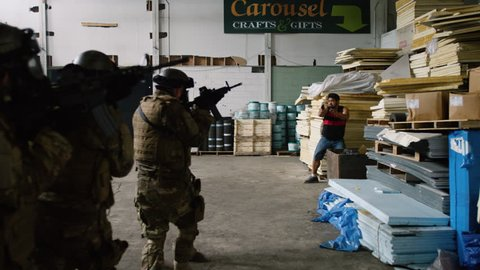 Special ops military SWAT team have shootout with villains in warehouse under dramatic daytime lighting. Daytime medium to closeup shot on 4K RED camera.