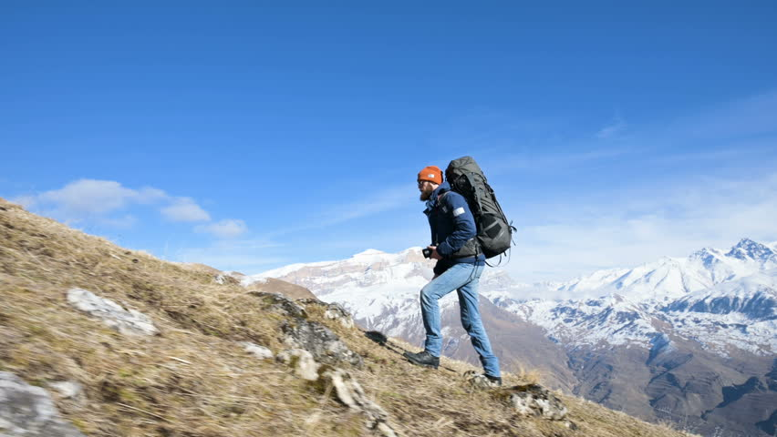 Bearded young male photographer in a hat and sunglasses with a large backpack and a camera around his neck climbs up the hill against the background of snow-capped mountains
