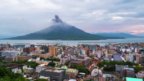 Kagoshima, Japan. View of mountain Sakurajima an active volcano. Aerial view of Kagoshima city in Japan at sunrise. Time-lapse with volcano eruption in the morning, zoom in