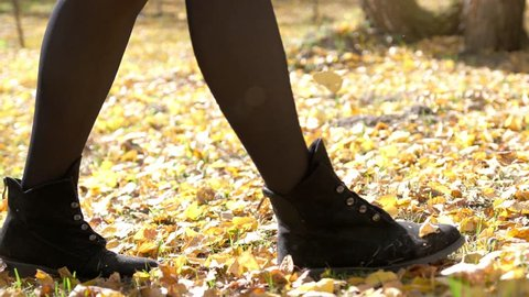 Female steps along the colorful autumn foliage of the city park. Walk in the autumn. Close up legs and shoes view. slow motion. 3840x2160