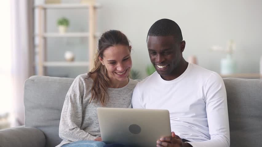 Happy mixed ethnicity young couple using laptop for ecommerce doing online shopping together watching video movie sitting on sofa, smiling african man and caucasian woman looking at computer at home