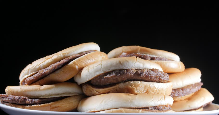 Rotating view of heaped plain beef patty burgers on flat buns stacked on a plate over a black background   Shutterstock HD Video #1027491872