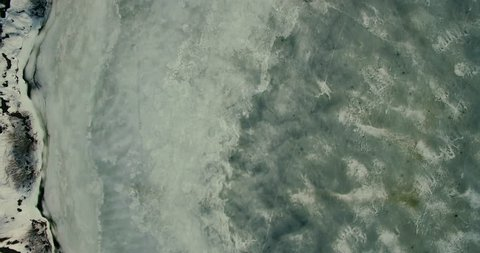 Aerial Frozen Pond.Drone Snowy Frozen Pond Or Lake.Top-Down Aerial Forwards Over A Frozen Pond.Aerial Footage Flying Low Over A Frozen Lake With Snowy Patterns.Aerial Drone Footage Of Icy River .