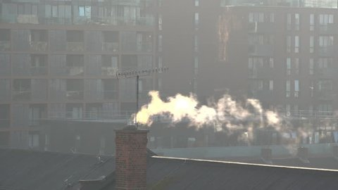 London, united kingdom (uk) - 10 18 2018: old chimney billows steam in  front of new luxury apartments