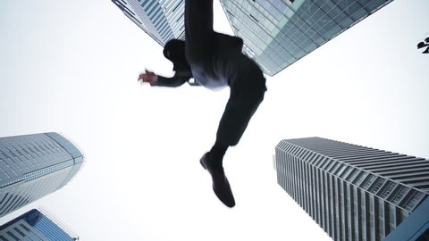 Jumping businesspeople in the city. Low angle view.