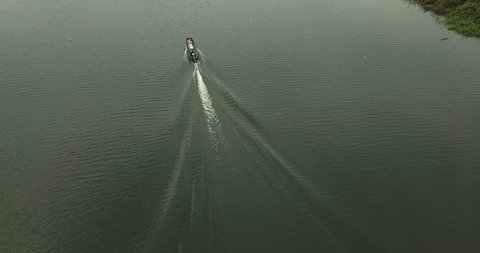 4K footage Aerial view, tilt shot follow a long tail boat in the lake of Mae Kuang Udom Thara dam, Chiang Mai, Northern Thailand.