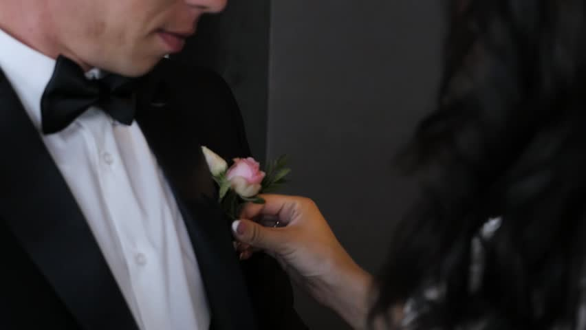 Bride straightens bowtie for groom's shirt #1027567712