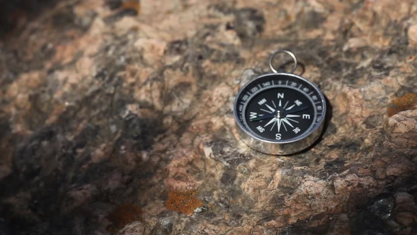 Magnetic compass with a black dial on a wild stone covered with moss.