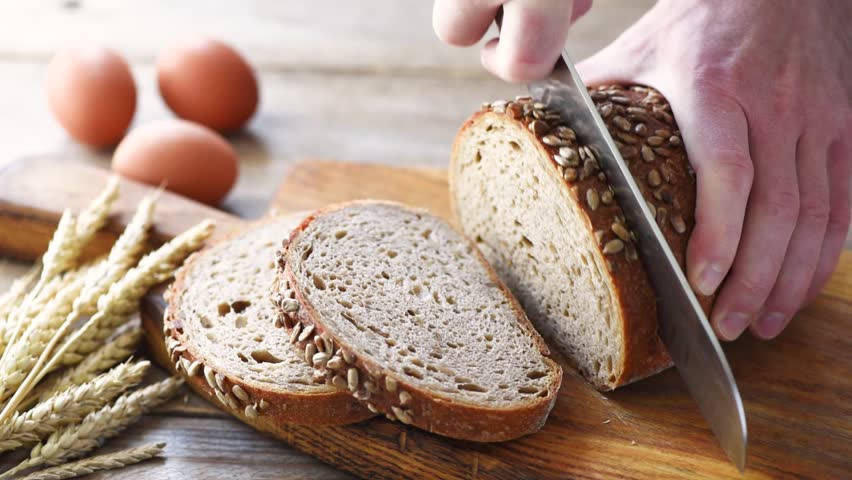 Closeup view of slicing bread on wooden cutting board. Sourdough bread sliced | Shutterstock HD Video #1027613012