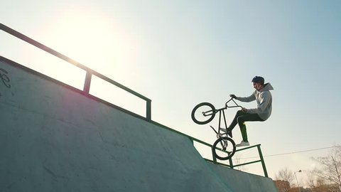 A bmx riders training their skills in the skatepark. Racing up, performing a flip and going down on a bright sun background