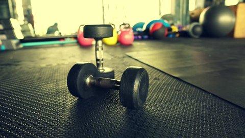 Taking dumbbells on ground in gym video 4k