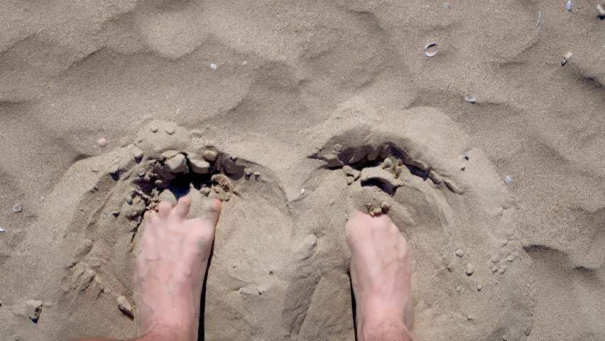 Man's feet bury in sand on beach on Sunny day. Concept of weekend and holiday.