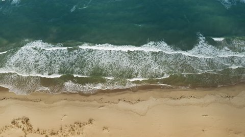 Scenic aerial view of golden sand waves and turquoise sea water with white foam from small waves. The concept of summer holidays. Bright abstract background perfect for any design. Drone slide up