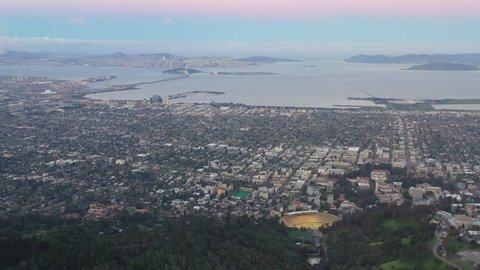 A clear, colorful dawn breaks over the East Bay hills and the city of Berkeley in the San Francisco Bay area of Northern California.