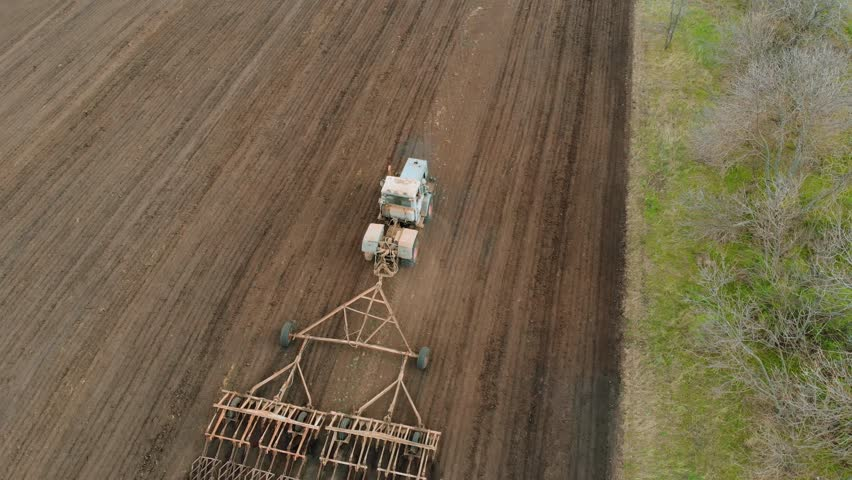 Large tractor with paired cultivator ploughs soil for sowing sunflower | Shutterstock HD Video #1027718972