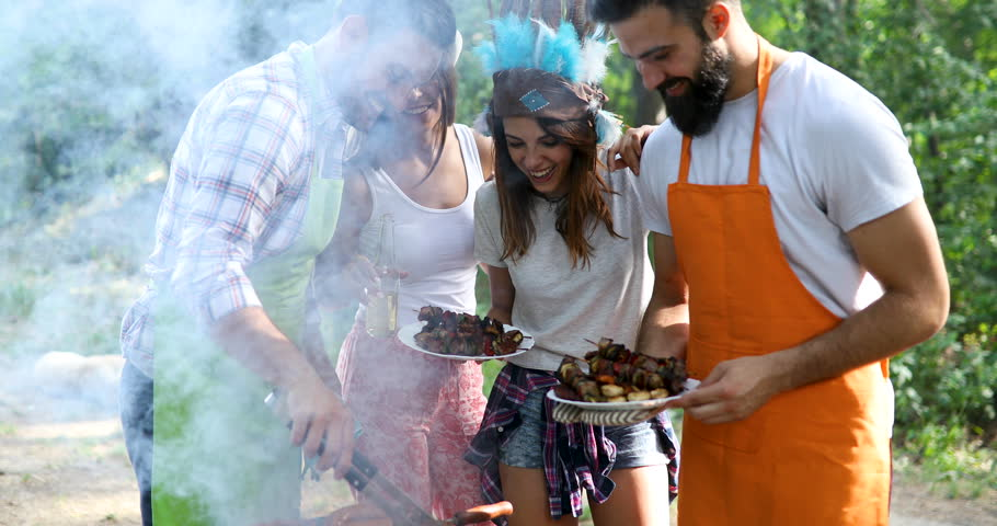 Happy friends having a barbecue party in nature   Shutterstock HD Video #1027720322