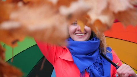 Slow motion. A young stylish longhaired blonde girl with a large colorful umbrella in a red coat in the autumn Park turns around smiling and throws an armful of yellow maple leaves.