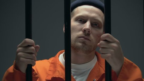 Imprisoned male holding bars and looking to camera, feeling guilty and desperate