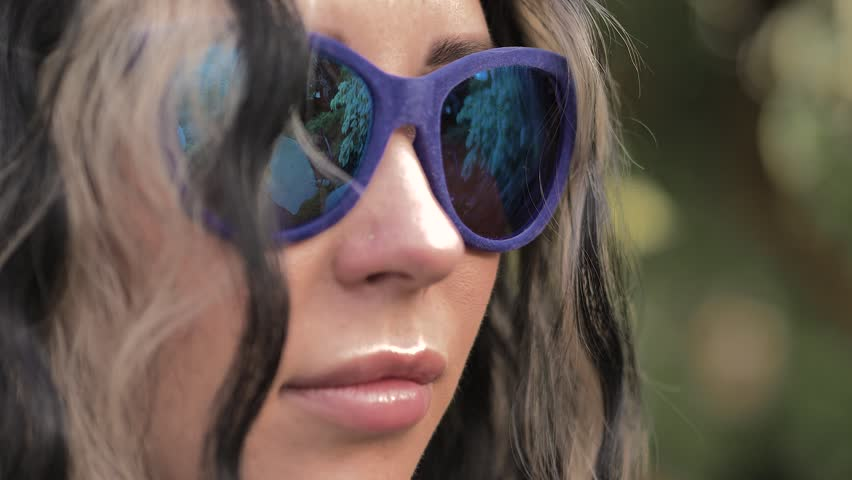 Portrait of a beautiful Caucasian brunette girl in blue sunglasses. In the mirror reflection a tree with white leaves is a ficus, a decorative bridge, a greenhouse.Looks to the side