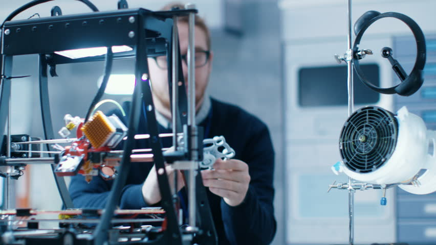 Young Talented Male Engineer In a Modern Laboratory Constructs Prototype with the Help of 3D Printer. | Shutterstock HD Video #1027774682