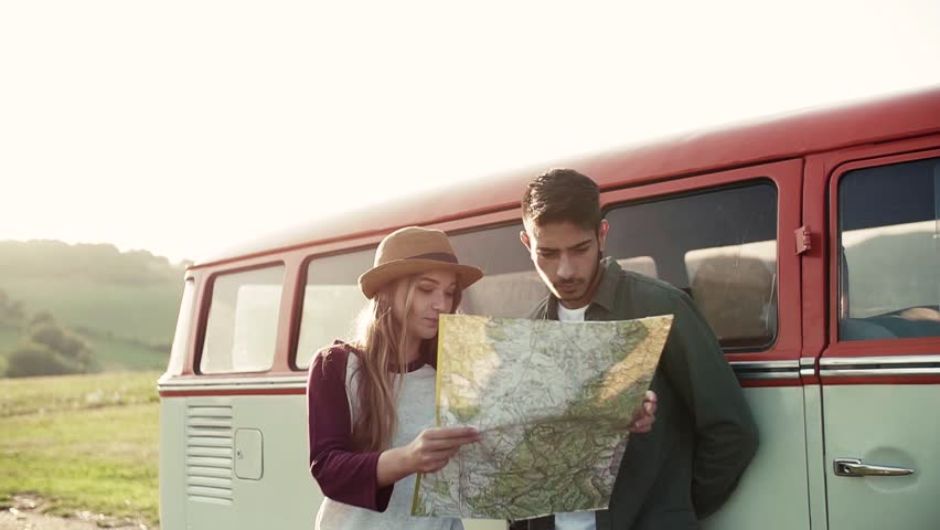 A young couple on a roadtrip through countryside, looking at a map. | Shutterstock HD Video #1027781822