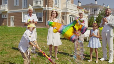 Happy multigenerational family in party hats clapping hands and smiling while watching little boy with blindfold hitting piñata with bat at birthday celebration outdoors on summer day