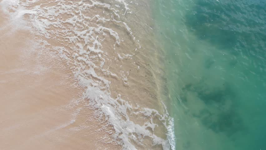 Aerial view waves break on white sand beach at sunset. Sea waves on the beautiful beach aerial view drone 4k shot. | Shutterstock HD Video #1027816772