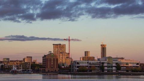 Stunning timelapse sunset in  Manchester salford quays with crane construction over river.