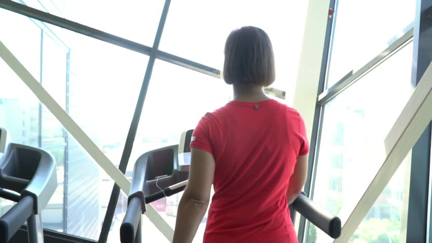 Attractive caucasian girl running on the treadmill in the sport gym with phone and earphones. Camera in 1920?1080. Slow motion . | Shutterstock HD Video #1027854482
