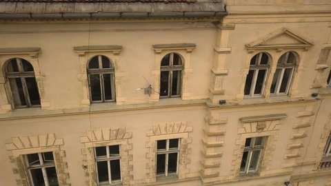 A rightward trucking drone shot, capturing a glimpse of a vintage architechture in a closed locality in the city of Sighisoara on an afternoon