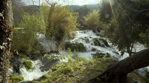 River flows over high ledge through reeds and grasses in afternoon light