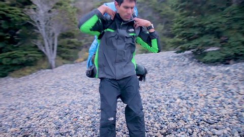 Hiking man putting on backpack in Torres del paine in patagonia ready to go