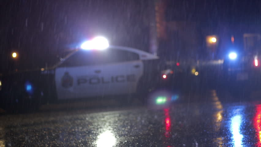 Emergency response police cars flashing light reflecting in the rain. Detectives close off the street during an active crime scene investigation. Police car in the rain.  | Shutterstock HD Video #1027897502