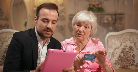 Loving couple of different ages shopping online together using tablet and credit card
