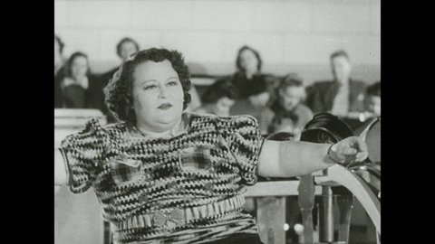 1930s: Woman sits at front of bowling lane, looks defeated, gets hit in head with ball, falls over. Girl in audience covers her eyes, peeks through. Woman prepares to bowl.