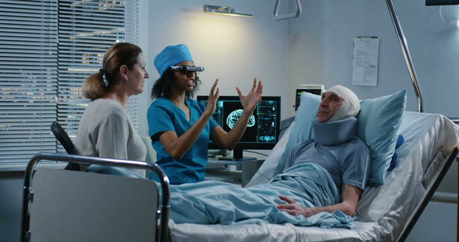 Medium shot of a young female doctor using VR headset during discussing diagnosis with patient and his relative | Shutterstock HD Video #1027955552