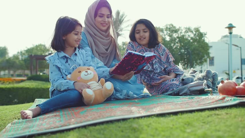 Mom and daughters spending time torgether at the park, playing at the playground and reading stories, Family moments in dubai