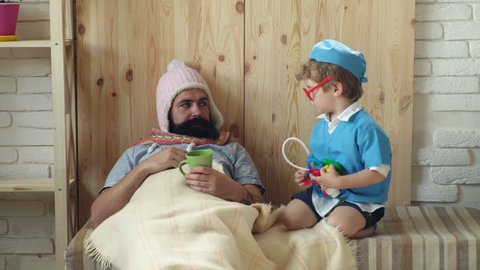 Doctor games concept. Doctor child in glasses with stethoscope examine father at home. Doctor boy in doctor uniform treat patient, game and development. Father and kid playing clinic