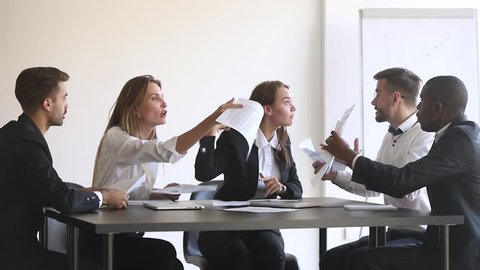Angry diverse team colleagues argue over paperwork shouting during company business group meeting, mad annoyed coworkers disputing about documents quarreling shouting dissatisfied with bad teamwork