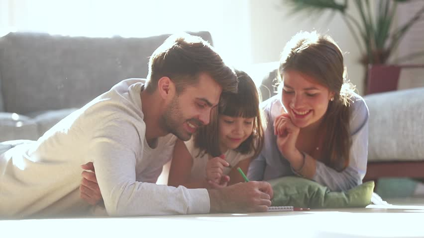 Happy family young parents drawing coloring picture with pencils helping cute child daughter enjoying talk play laying on warm floor at home, mom dad and kid girl having fun in living room on leisure | Shutterstock HD Video #1028009672