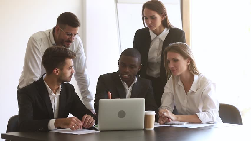 African coach leader showing online computer project consulting partners, black mentor teaching team employees training diverse corporate group working on laptop talking in teamwork at office meeting | Shutterstock HD Video #1028009762