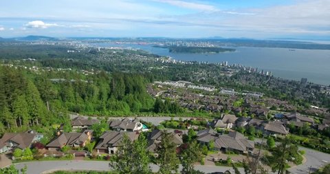 VANCOUVER, CANADA. Aerial view over the sea and mountains by the British Columbia's coast. The metropolitan area surrounded with North Shore Mountains.