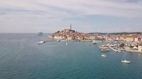 Long aerial footage of Rovinj. Wide open area with marina, fly above old town and cruise ship.