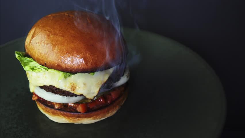 Fresh smoky appetizing cheeseburger rotating in 4k.   Shutterstock HD Video #1028018762