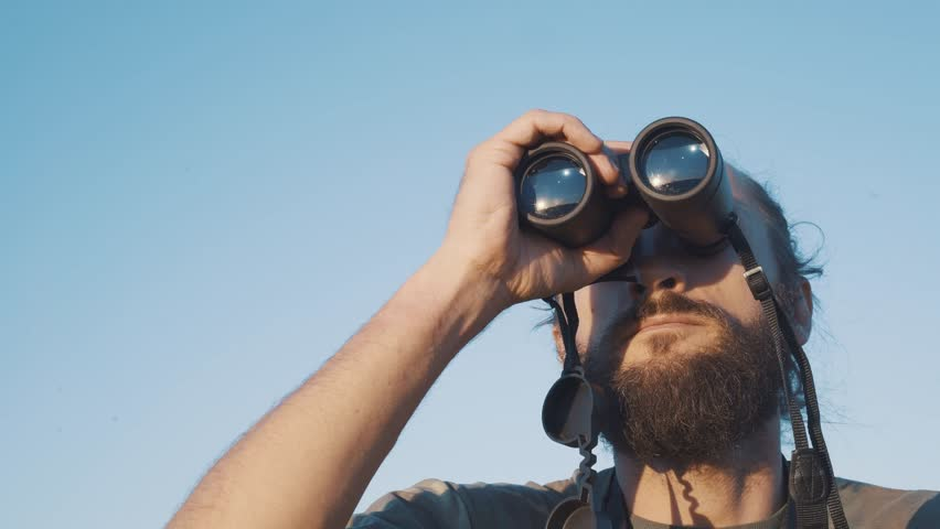 A bearded masculin man in military t-shirt looks through binoculars. Concept: new horizons, development, travel, territory explorer, adventure time, birdwatching, hunting. close up | Shutterstock HD Video #1028020952