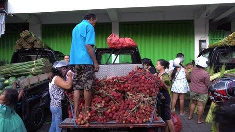 BALI/INDONESIA-APRIL 20 2019: Rambutan sellers are selling rambutan from the top of their car. Rambutan fruit is a typical Indonesian fruit. The fruit is sweet and slightly sour taste